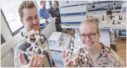 PhD student Mikkel Agerbæk Sørensen from the Department of Chemistry and Postdoc Ursula Bengård Hansen from the research group X-ray and Neutron Science at the Niels Bohr Institute shows a 3D model of the studied molecule. By making small changes in the form of the molecule, the tunnelling can be suppressed. In the background Associate Professor Kim Lefmann and Professor Jesper Bendix. Photo: Ola J. Joensen